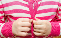 Little girl buttoning her jacket Stock Photos