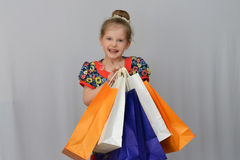 The little girl, the buyer holds the colored shopping bags. Royalty Free Stock Photography