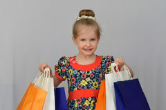 The little girl, the buyer holds the colored shopping bags. Stock Photography