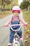 Little girl on bycicle Stock Images
