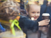 Little girl in a cafe with a paper Cup Royalty Free Stock Photo