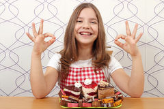 Little girl with cakes and ok hand sign Stock Photography