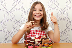 Little girl with cakes and thumb up Stock Photo