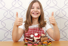 Little girl with cakes and thumbs up Stock Photo