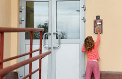 Little girl calling in on-door speakerphone Royalty Free Stock Image