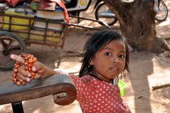 Little girl from Cambodia. August 2012, Siem Reap (Cambodia) - Poor little girl in front of Angkor Wat monument trying to sell some bracelets Royalty Free Stock Images