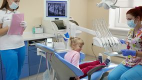 Little girl came to female stomatologist treat teeth in dentist`s office with modern equipment. Little girl came to female stomatologist treat teeth in light stock video footage