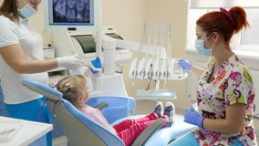 Little girl came to stomatologist and sits down in dental armchair next to instruments and equipment. In bright office stock footage
