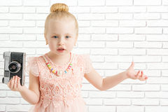 Little girl with camera made helpless gesture Stock Photos