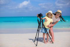 Little girl with camera and young mother on beach Royalty Free Stock Photography