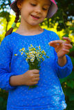 Little girl with camomile flowers Royalty Free Stock Image