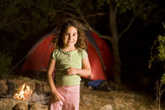 Little girl at a camp. At night infront of a red tent and a campfire Stock Images