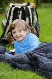 Little girl camping laying on a sleaping bag Stock Photo