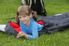 Little girl camping with sleeping bag. A happy little girl camping with sleeping bag Royalty Free Stock Photos