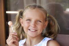 Little girl with candy joyful portrait Stock Photos