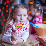 Little girl with candy preparing Christmas cakes Royalty Free Stock Images