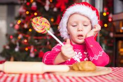 Little girl with candy preparing Christmas cakes Stock Photo