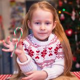 Little girl with candy preparing Christmas cakes Royalty Free Stock Photo