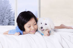 Little girl and canine lying in the bed Stock Image