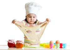 Little girl in cap of the cook playing with dough Royalty Free Stock Images