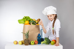 Little girl in a cap cook a variety of fresh food. Girl with a variety of fresh vegetables and fruits. Royalty Free Stock Photo