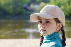 Little girl in a cap portrait. Little girl in a cap on nature portrait Stock Image