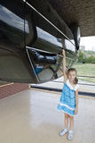 Little girl with the car in attraction Inverted house. Stock Photo