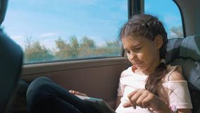 Little girl in the car with a tablet internet social media goes on a trip . girl in car concept travel transport. Little girl in the car with tablet internet stock video footage
