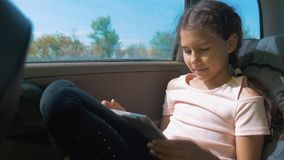Little girl in the car with a tablet internet social media goes on a trip . girl in car concept motion travel transport. Little girl in the car with tablet stock video footage