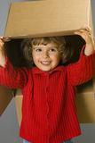 Little girl with cardboard box. Little girl play with cardboard box royalty free stock images