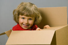 Little girl with cardboard box. Little girl play with cardboard box stock photography