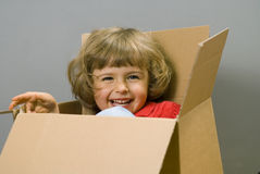 Little girl with cardboard box. Little girl play with cardboard box royalty free stock photography