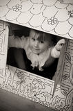 Little girl in cardboard house stock photos