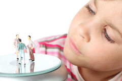 Little girl carefully looks at small toy figures Royalty Free Stock Image