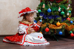 Little girl in carnival costume holding Christmas ball Stock Photography