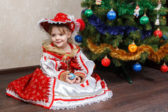 Little girl in carnival costume holding Christmas ball Royalty Free Stock Photo