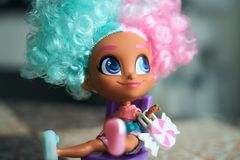 Little girl in carnival costume. Fashion doll on a chair, children`s toys stock photography