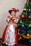 Little girl in carnival costume near Christmas tree Stock Images