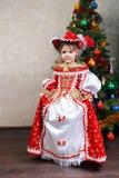 Little girl in carnival costume near Christmas tree Stock Photo