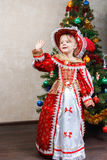 Little girl in carnival costume waving near Christmas tree Stock Photography