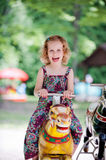 Little Girl on Carousel Horse Stock Images