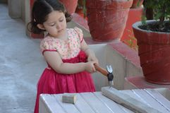 Little Girl Carpenter. Hammering a nail outdoors. Indian, Asian Royalty Free Stock Photography