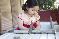 Little Girl Carpenter. Little girl sawing plank with a handsaw outdoors. Indian, Asian Royalty Free Stock Images