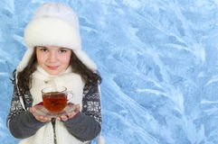 Little girl carries a cup of tea on winter background. Smiling little girl carries a glass cup of black tea on frozen winter background Stock Images