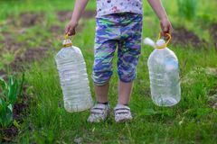 A little girl is carrying bottles Royalty Free Stock Photography