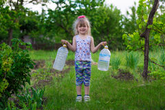 A little girl is carrying bottles Royalty Free Stock Image