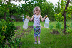 A little girl is carrying bottles Royalty Free Stock Photos