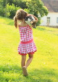 Little girl carrying a dog Royalty Free Stock Images