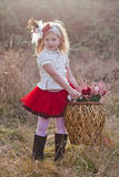 Little girl carrying large wickerwork basket Royalty Free Stock Image