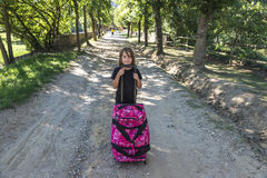 Little girl carrying a suitcase Royalty Free Stock Photo